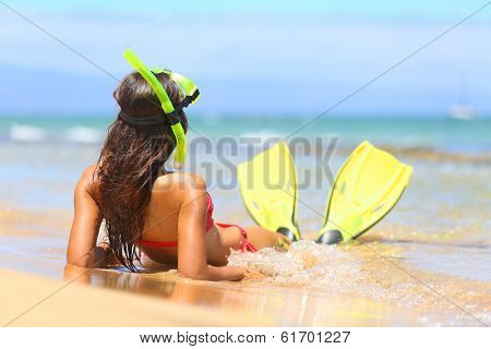 Woman relaxing on summer beach vacation holidays lying in sand with snorkeling mask and fins smiling happy enjoying the sun on sunny summer day on Maui, Hawaii, USA.
