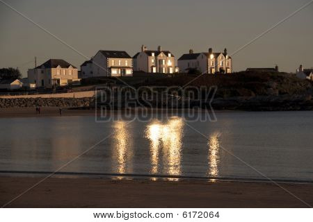 Trearddur Bay sunset with the sun reflecting off the houses back on to the sea poster