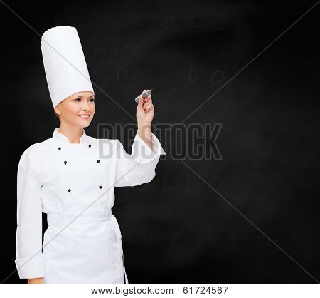 cooking, new techology , advertisement and food concept - smiling female chef with marker writing something on virtual screen
