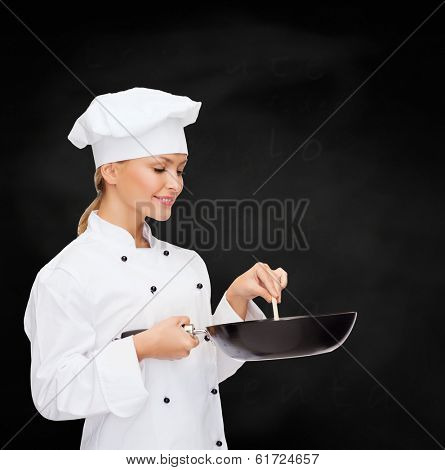 cooking and food concept - smiling female chef, cook or baker with pan and spoon
