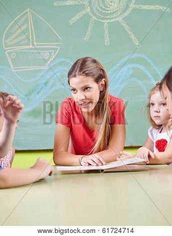 Nursery teacher reading book for children in a kindergarten