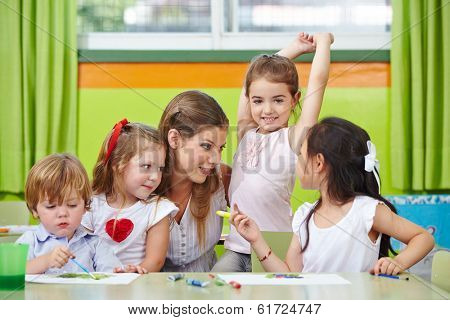 Children talking to nursery teacher in kindergarten while painting pictures