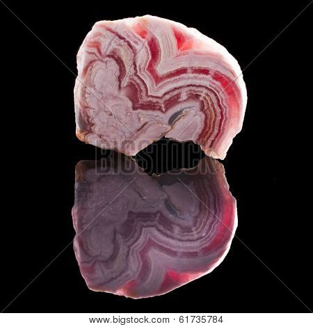 Rhodochrosite stone with reflection on black surface background