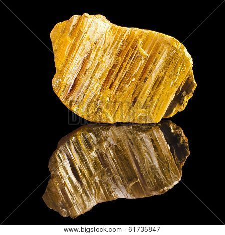 Orpiment with reflection on black surface background