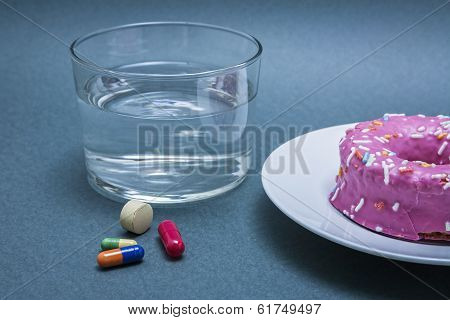 Various Medicines To Combat Diabetes Along With A Sweet Cake And Glass Water