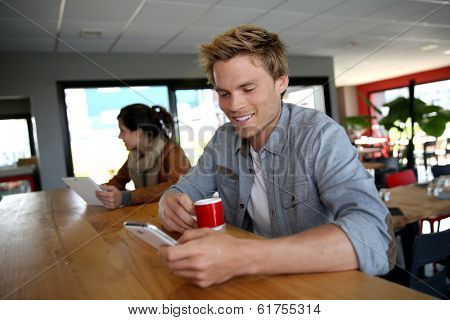 Young man in coffee shop wonnected on smartphone
