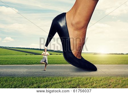 small calm woman under big female heel