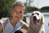 Beautiful curly blond woman sitting with her dog by the waterside poster
