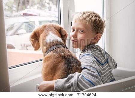 Little Boy With His Dog Waiting Together Near The Window