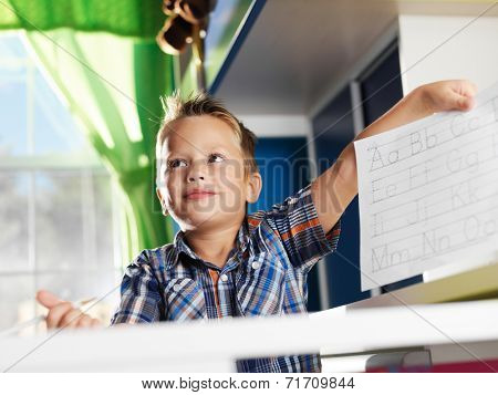 cute little boy showing his completed homework