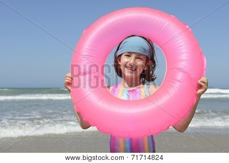 summer fun portrait: child with inflatable swimming ring at the beach