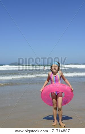 summer fun portrait: kid with inflatable swimming ring at the beach