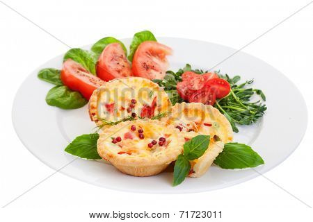 Plate of Mini quiche on a white background filled with vegetables with salad.Focus on the front pies.