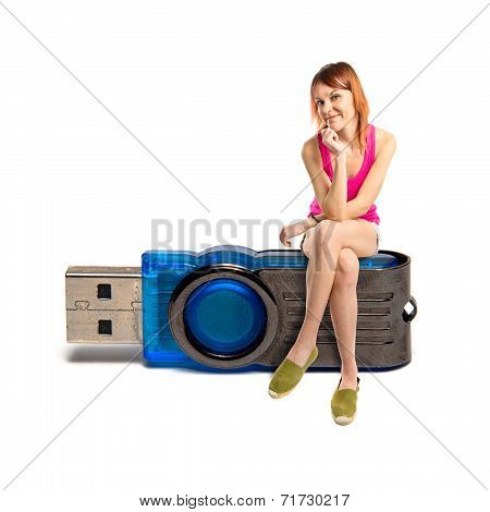 Redhead Girl Sitting On Pendrive Over White Background