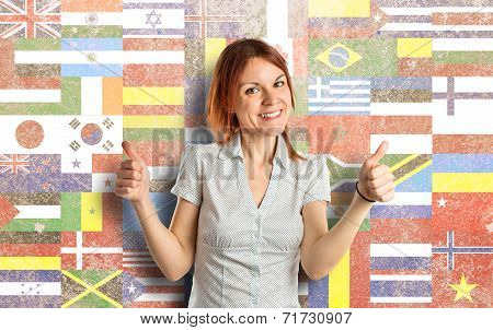 Pretty Young Girl With Thumbs Up Over Flags Background