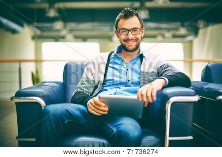 Smart businessman with touchpad sitting in office
