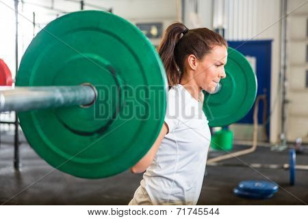 Side view of fit young woman lifting barbell in fitness box