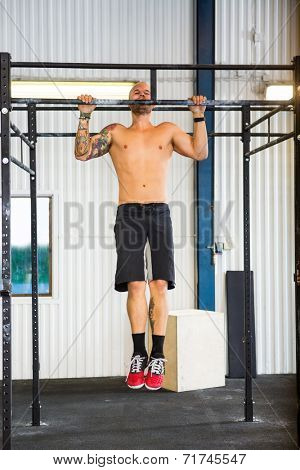 Full length of young male athlete doing chin-ups at healthclub