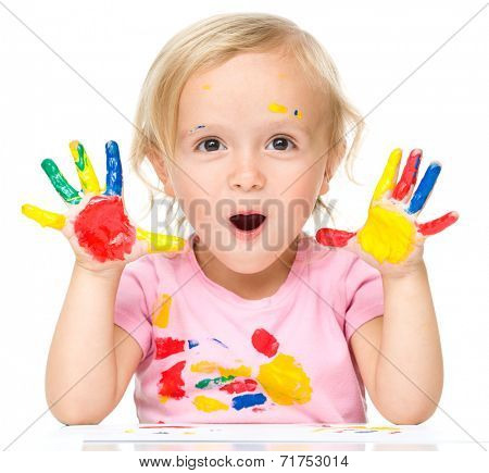 Portrait of a cute little girl showing her hands painted in bright colors, isolated over white