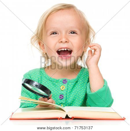 Little girl is reading her book using magnifier, isolated over white
