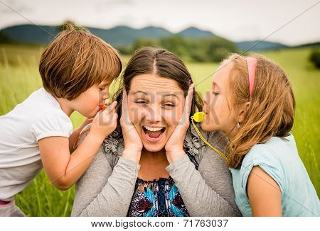 Children blowing whistle to mother's ears