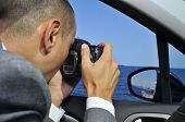 a detective or a paparazzi taking photos from inside a car poster