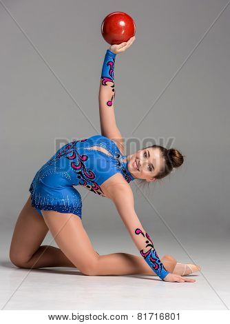 teenager doing gymnastics exercises with red gymnastic ball on a gray background poster