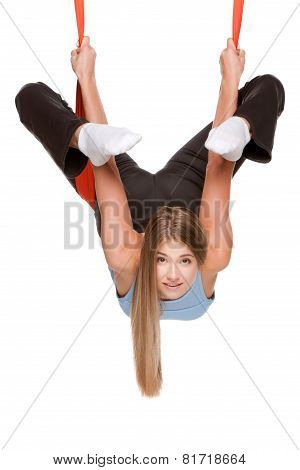 Young woman doing anti-gravity aerial yoga in red hammock on a seamless white background. poster
