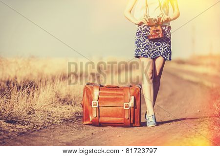 girl with suitcase and camera on country road.