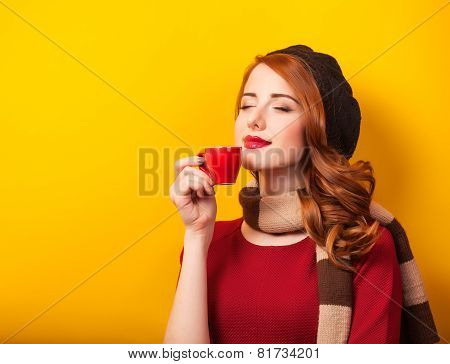 Redhead Girl With Red Cup Of Coffee Or Tea On Yellow Background.
