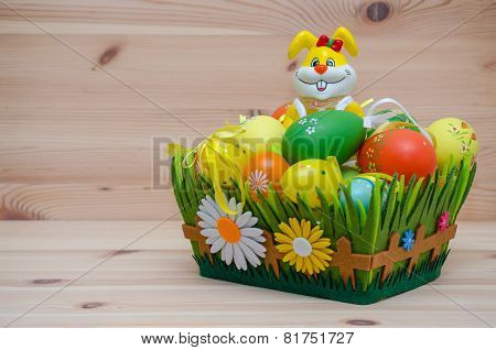 happy easter bunny with eggs in a basket on the wooden background