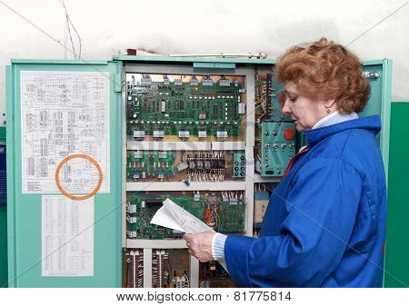 Operator woman-engineer in machine room (elevator) near electronic cabinet. poster