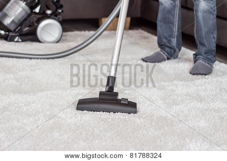 A man cleans the carpet with a vacuum cleaner.