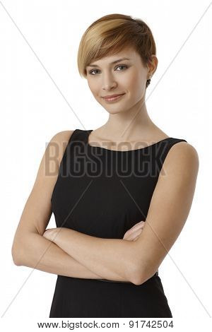Portrait of confident young woman in black dress with arms crossed, isolated on white background