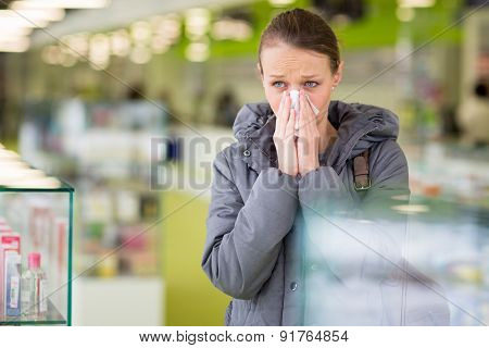 Young woman blowing her nose while in a modern pharmacy, choosing pills to help her with the flu/cold (shallow DOF; color toned image)