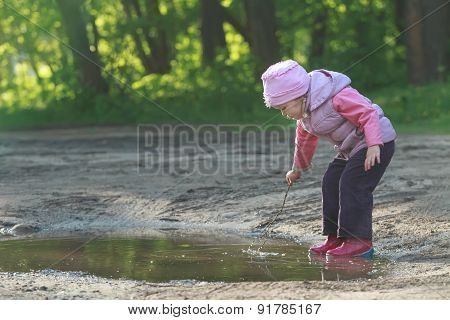 Toddler Preschooler Exploring Summer Puddle Wearing Red Gums Thin Tree Twig In Hand