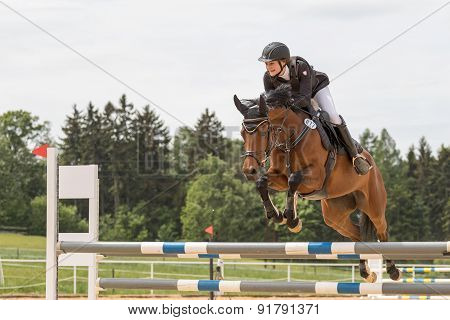Happy Young Horsewoman Is Jumping Over The Hurdle