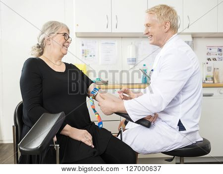 Smiling Doctor Collecting Senior Patient's Blood For Test In Clinic