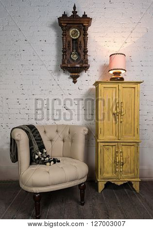 Still life of vintage beige armchair yellow cupboard wooden pendulum clock and illuminated table lamp on a wooden floor and white bricks wall