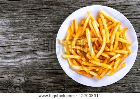 Tasty french fries on white plate on wooden table background blank space left top view