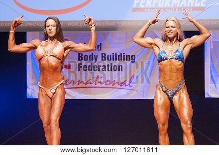 MAASTRICHT THE NETHERLANDS - OCTOBER 25 2015: Female fitness models Kinga Golebiewska and another competitor flex their muscles and show their best physique in a front double biceps pose on stage at the World Grandprix Bodybuilding and Fitness
