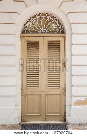 An old weathered french window with closed shutters