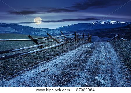 carpathian mountain peaks in snow above green rural meadow near the road with wooden fence
