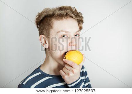 Young Boy About To Bite A Fresh Lemon