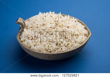 jeera rice, long-grain basmati rice flavoured with fried cumin seeds , served in a ceramic bowl, top view, isolated and front view on orange background
