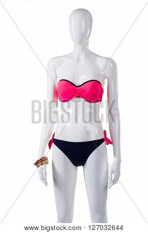 Bicolor swimsuit and bracelets. Female mannequin in bicolor swimwear. Pink top with black bottom. Lady's attractive swimwear on display.
