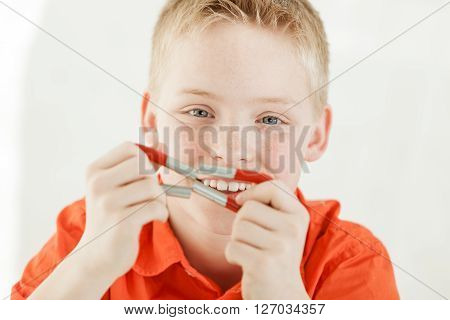 Cheerful Boy Holds Magnets Together By His Face
