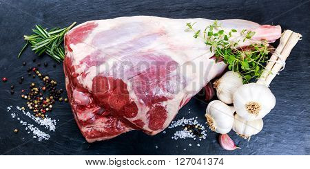 Raw lamb leg on blue stone background with herbs.