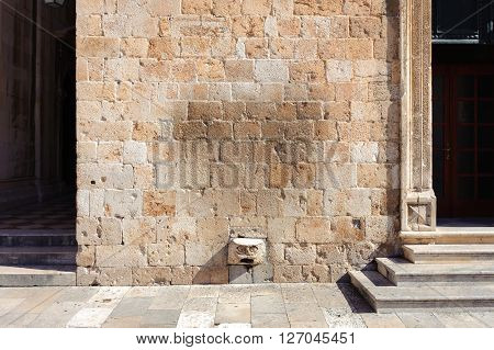 Protruding stone with carved face at the Franciscan monastery where fortune favors whoever manages to stand on it.