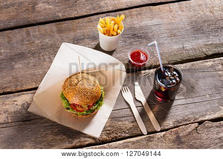 Hamburger with cola and fries. Cola glass and burger. Fast food and tomato sauce. Your daily calorie norm.